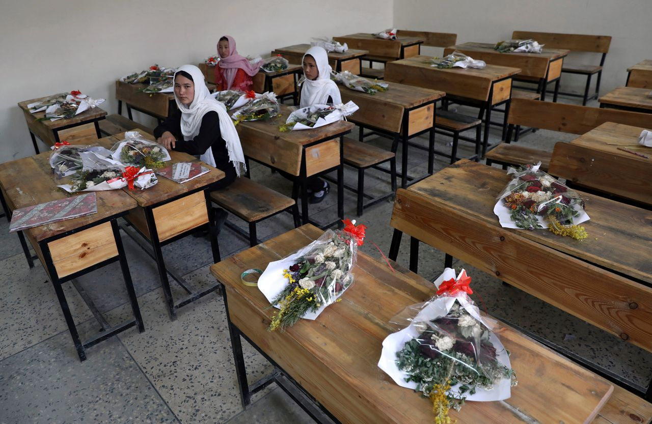 Afghaanse kinderen zitten in een klaslokaal van de Syed Al-Shahd meisjesschool in Kaboel, die op 8 mei gebombardeerd werd. Op de lege tafels liggen boeketten als eerbetoon aan de slachtoffers.