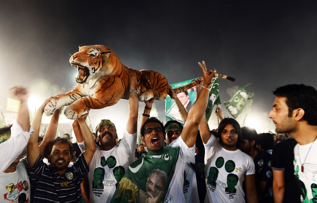 Supporters cheer former Pakistani Prime Minister cheer with a stuffed toy tiger at a campaign closing rally in Lahore on May 9, 2013, two days before some 86 million registered voters will go to the polls to elect lawmakers to the lower house of parliament and four provincial assemblies. The frontrunner in Pakistan's election campaign, former Prime Minsiter Nawaz Sharif, gave an impassioned final speech to thousands of supporters today, promising to change the country's course if elected. Pakistan's general elections will mark the first democratic transition of power in the country's 66-year existence. AFP PHOTOS/ARIF ALI