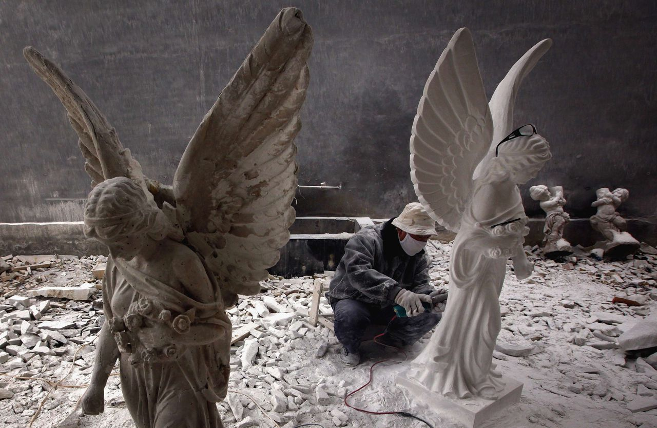 A sculptor works on statues of angels in an outdoor workshop in the town of Dangcheng in Quyang county, located 250 km (155 miles) southwest of Beijing December 7, 2011. The small town situated in Hebei province has a history of stone carving dating back more than two thousand years. It is finding business in the current economic climate tough with the combination of a large raise in worker's wages and the world economic slump that continues to suck away orders for the ornate stone statues, busts and carvings. Statues of Jesus and copies of ancient Roman busts now far outnumber the workers who chip and grind away in the small workshops. REUTERS/David Gray (CHINA - Tags: SOCIETY BUSINESS EMPLOYMENT)