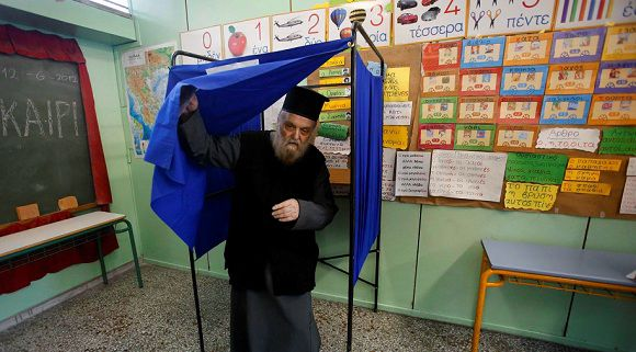Caption: A Greek orthodox priest holds his ballot paper as he exits a voting booth at an Athens primary school used as a polling station June 17, 2012. Voting opened on Sunday in a Greek election that could decide whether the heavily indebted country remains in the euro zone or heads for the exit, potentially unleashing shocks that could break up the single currency. REUTERS/Yannis Behrakis (GREECE - Tags: POLITICS ELECTIONS BUSINESS)