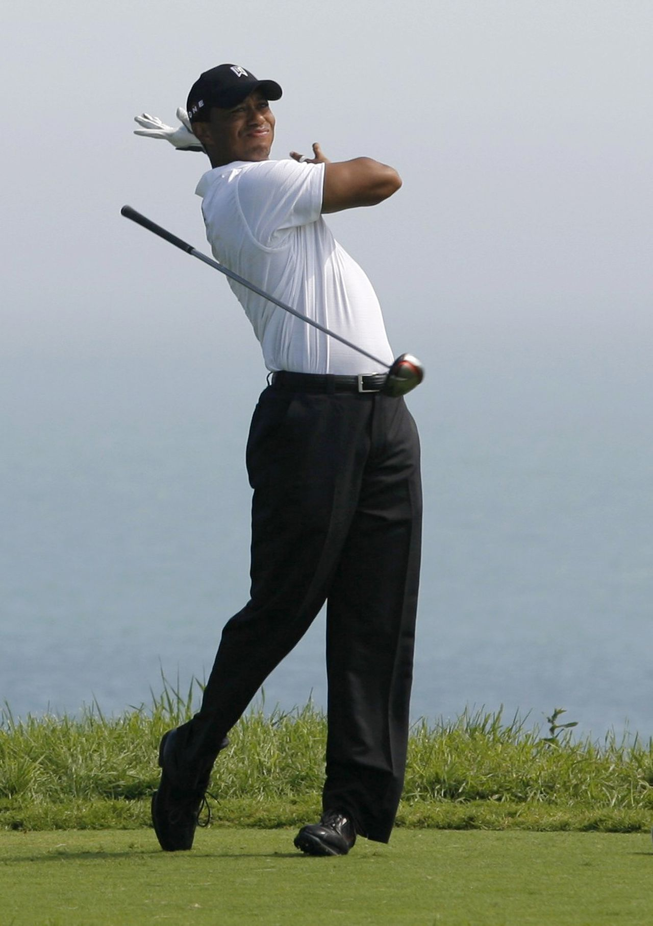 Tiger Woods of the U.S. lets go of his club after hitting on the fifth tee during the first round of the 92nd PGA Golf Championship at Whistling Straits in Kohler, Wisconsin, August 12, 2010. REUTERS/Matt Sullivan (UNITED STATES - Tags: SPORT GOLF IMAGES OF THE DAY)