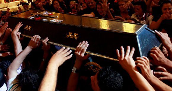 Caption: Egyptian Coptic Christians carry coffins during a mass funeral for victims of sectarian clashes with soldiers and riot police at a protest against an attack on a church in southern Egypt at Abassaiya Cathedral in Cairo October 10, 2011. Thousands of mourners attend a funeral ceremony for those killed in overnight clashes when troops crushed a protest over an attack on a church in the worst violence since the uprising that toppled Hosni Mubarak. REUTERS/Amr Abdallah Dalsh (EGYPT - Tags: CIVIL UNREST POLITICS RELIGION)