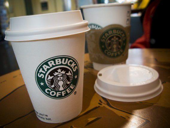 Medewerkers van Starbucks gaan op de koffiebekers politici oproepen tot elkaar te komen in het debat over de 'fiscal cliff''. Foto ANP / Lex van Lieshout