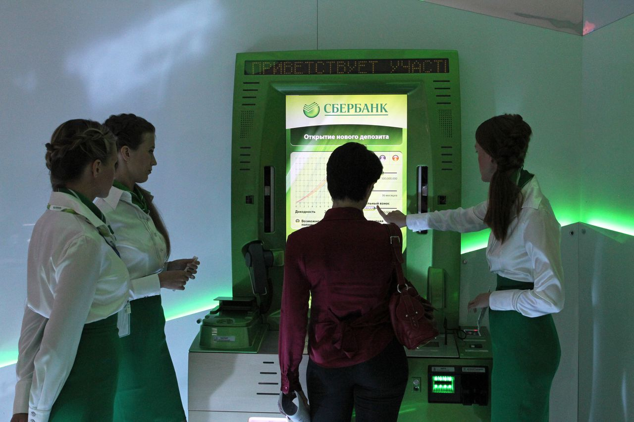 Employees operate a lie-detecting automated teller machine (ATM) on the OAO Sberbank stand at the St Petersburg International Economic Forum (SPIEF), in St Petersburg, Russia, on Thursday, June 16, 2011. The forum sees global world and business leaders gather in Russia for a conference beginning today through Saturday, June 18. Photographer: Andrey Rudakov/Bloomberg