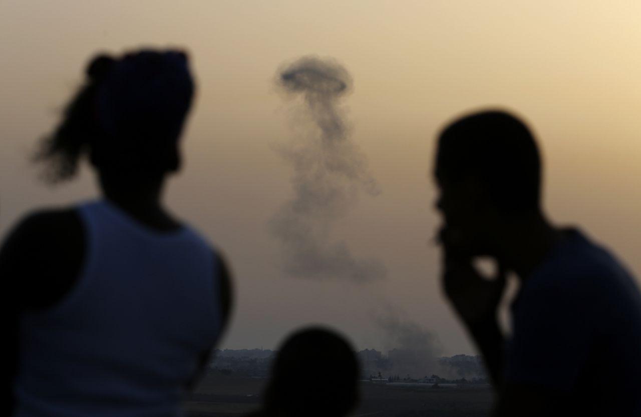 Israëli's kijken uit over de Gazastrook waar rook opstijgt na een luchtaanval.