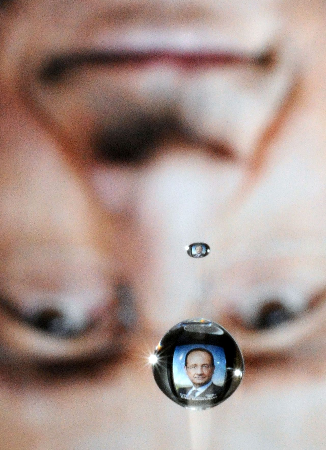 A picture taken on May 4, 2012 in Marseille, southern France, shows a drop of water that reflected the campaign poster of France's Socialist Party (PS) candidate for the 2012 French presidential election Francois Hollande , two days ahead of the second round of the election. AFP AFP PHOTO / GERARD JULIEN