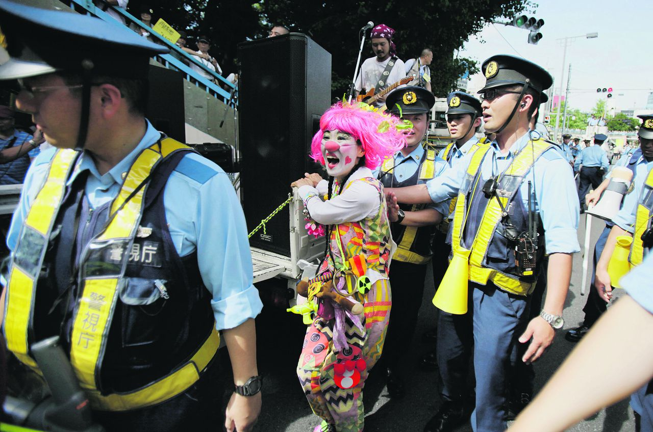 "An anti-nuclear protester dressed as a clown is moved on by police during a march through downtown Tokyo, Monday, July 16, 2012. Tens of thousands of people gathered at a Tokyo park, demanding ""Sayonara,"" or goodbye, to nuclear power as Japan prepares to restart yet another reactor, and expressed outrage over a report that blamed culture on the Fukushima disaster. (AP Photo/Greg Baker)"