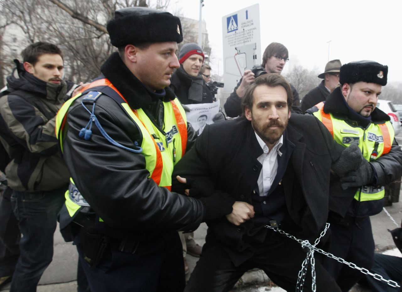 Police try to remove Gabor Vago, one of the lawmakers from the opposition LMP party who chained themselves together to prevent lawmakers from entering the parliament building to vote on proposed new electoral and public finance laws, in Budapest December 23, 2011. Hungary plans to pass laws on Friday to revamp the electoral system and an economic law strongly objected by the EU, which the LMP party say are a blow to democracy. REUTERS/Laszlo Balogh (HUNGARY - Tags: CIVIL UNREST POLITICS BUSINESS)