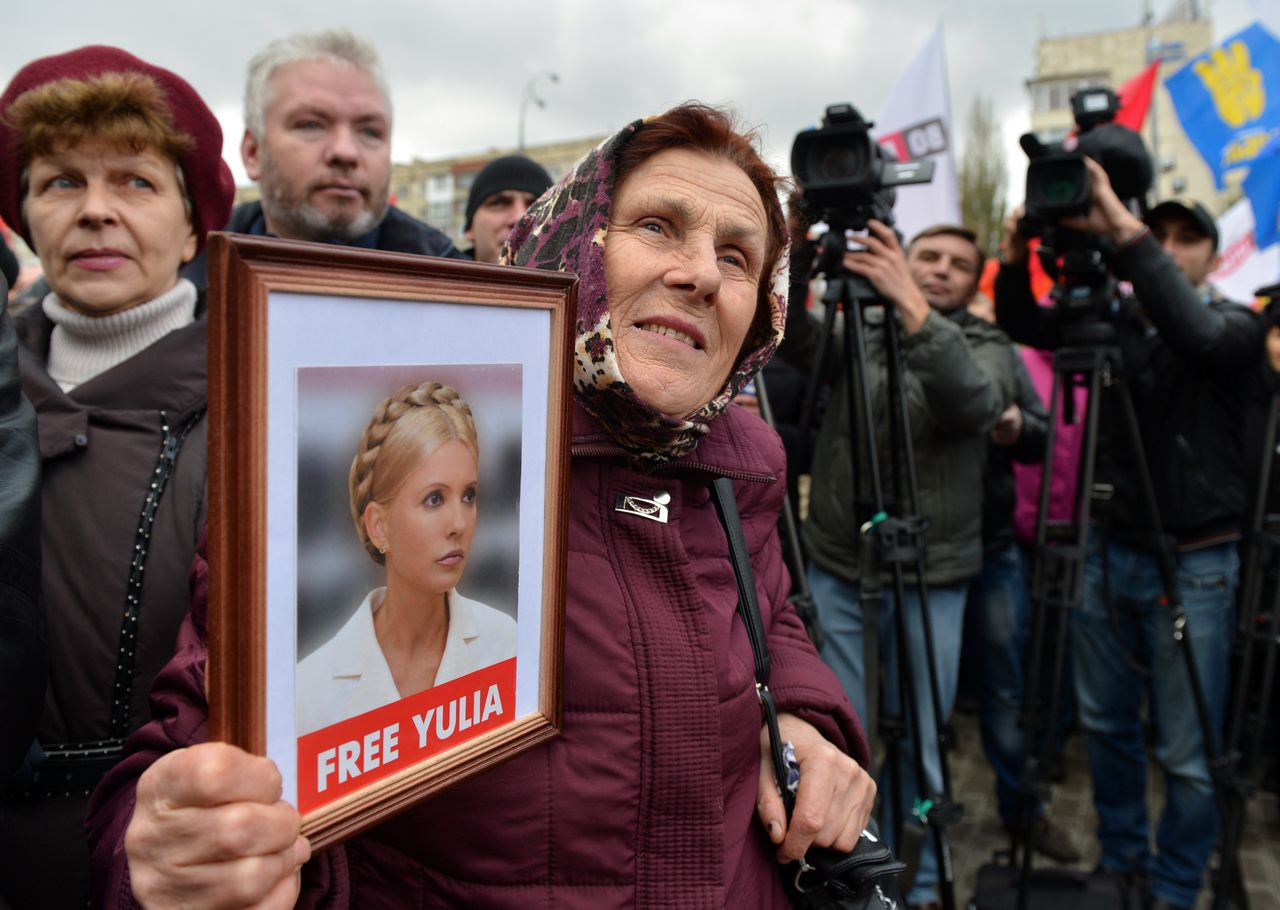 A protester holds a framed photo of jailled Ukrainian former prime minister Yulia Tymoshenko during an opposition rally in front of the central election commission in Kiev on November 6, 2012. Election officials in Ukraine on November 5 called a re-vote in five districts as thousands of people protested in central Kiev against alleged fraud in parliamentary elections won by the ruling party. The central election commission told parliament to set a date for new polls in the five districts, saying in a statement cited by the Interfax news agency that it was impossible to conclusively establish the outcome there because of numerous irregularities in the October 28 polls. AFP PHOTO / SERGEI SUPINSKY