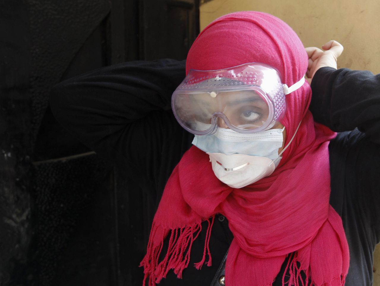 A female protester adjusts protective gear during clashes with riot police in a side street near Tahrir Square in Cairo November 22, 2011. REUTERS/Goran Tomasevic (EGYPT - Tags: POLITICS CIVIL UNREST)