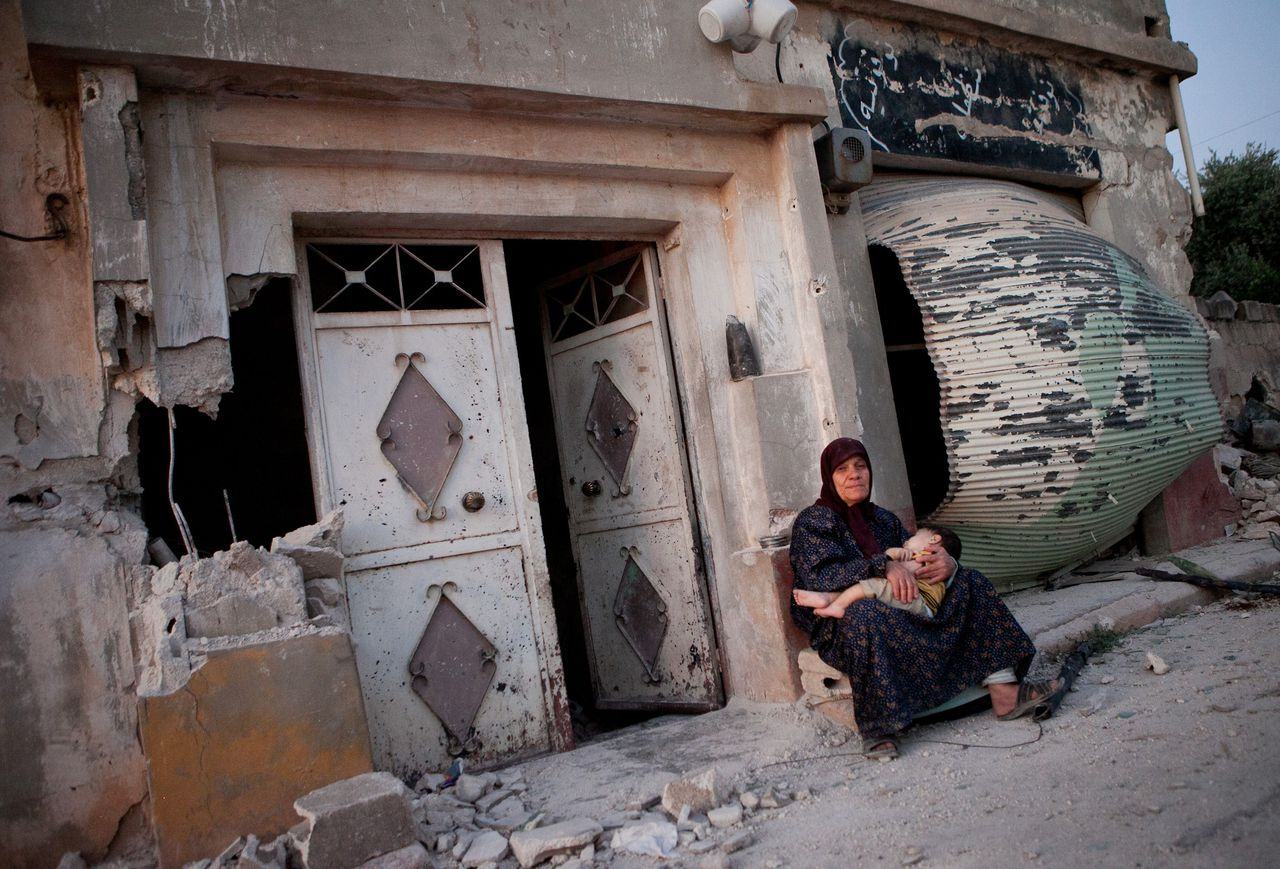 TOPSHOTS A Syrian woman sits with her grandson outside a damaged building on the main street of the Syrian village of Treimsa, where more than 150 people were killed this week, in the central province of Hama on July 13, 2012. A variety of weapons were used in the attack on Treimsa, with the homes of rebels and activists bearing the brunt, UN observers said. AFP PHOTO/D. LEAL OLIVAS