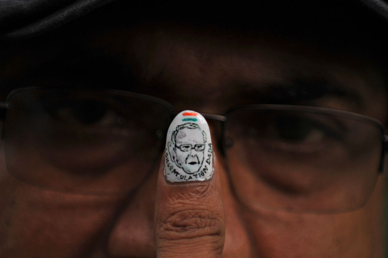Indian artist Ramesh Sah shows his painted thumb nail with a miniature portrait of former finance minister and Indian presidential candidate Pranab Mukherjee in Siliguri on June 27, 2012. Indian Finance Minister Pranab Mukherjee stepped down June 26, leaving behind a faltering economy and a plunging rupee as he sets his sights on the country's presidency. AFP PHOTO/Diptendu DUTTA