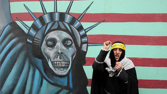 Caption: A female Iranian teacher chants anti-US slogans, in front of a satirized drawing of the Statue of Liberty, painted on the wall of the former US Embassy in Tehran, Iran, in an annual state-backed rally, on Friday, Nov. 4, 2011, marking the anniversary of the seizure of the US Embassy by militant students on Nov. 4, 1979, when militant Iranian students who believed the embassy was a center of plots against the Persian country held 52 Americans hostage for 444 days. The US severed diplomatic ties in response, and the two countries have not had formal relations since. (AP Photo/Vahid Salemi)