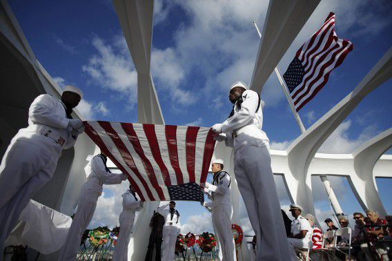 The U.S. Navy Region Hawaii Ceremonial Guard prepares the flag for Joann Olsen during the internment ceremony of her husband, USS Arizona survivor Vernon J. Olsen, aboard the USS Arizona Memorial during the 70th anniversary of the attack on Pearl Harbor at the World War II Valor in the Pacific National Monument in Honolulu, Hawaii December 7, 2011. REUTERS/Hugh Gentry (UNITED STATES - Tags: ANNIVERSARY CONFLICT)
