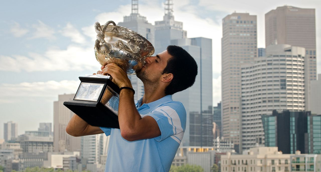 Serbia's Novak Djokovic kisses the Australian Open tennis tournament championship trophy as he poses for photographers in Melbourne on January 31, 2011. Djokovic defeated Britain's Andy Murray in the men's singles final on January 30, 2011. IMAGE STRICTLY RESTRICTED TO EDITORIAL USE ? STRICTLY NO COMMERCIAL USE TOPSHOTS AFP PHOTO / Nicolas ASFOURI
