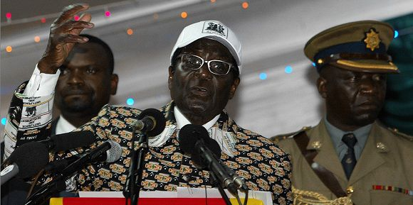 "Caption: Zimbabwe's President and leader of ZANU-PF Robert Mugabe (C) delivers a speech at the party's 12th National People's Conference in Bulawayo, on December 10, 2011. Mugabe said Saturday that he has no intention of retiring, saying doing so would be an act of ""cowardice."" AFP PHOTO/ JEKESAI NJIKIZANA"