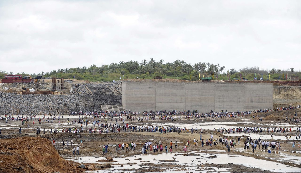 Invitees and workers walk at the basin of an under construction port at Hambantota on August 15, 2010, as it is being filled with sea water. Sri Lankan President Mahinda Rajapakse presided over a ceremony marking the construction of sea walls of the 1.5 billion dollar Chinese-founded construction. AFP PHOTO/Ishara S.KODIKARA