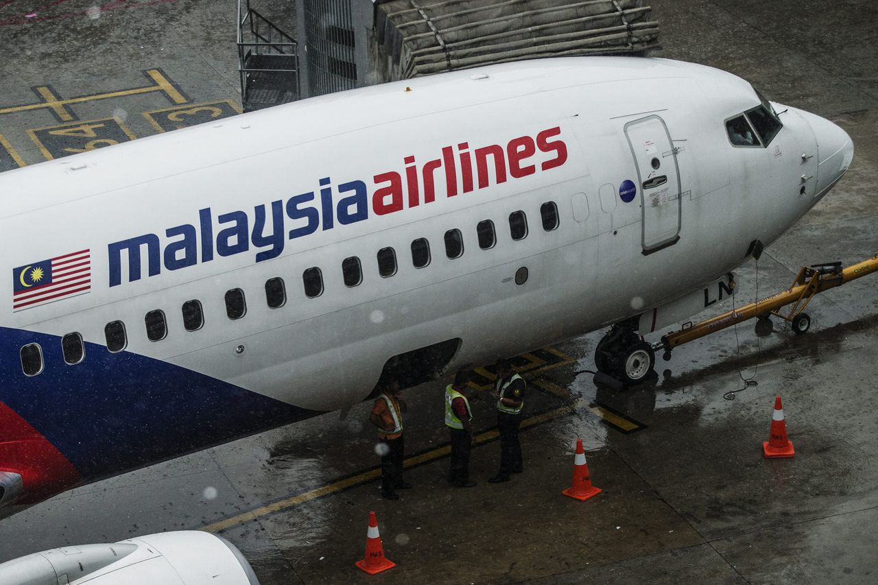 epa04345261 Malaysia Airlines crew work near their aircraft at Kuala Lumpur International Airport (KLIA), in Sepang outside Kuala Lumpur, Malaysia, 08 August 2014. Malaysia Airlines suspended the trading of its shares at the Kuala Lumpur stock exchange on 08 August 2014 and announced it will be removed from the stock market. Malaysia Airlines System Bhd was to be delisted in the first stage of a restructuring plan, its majority shareholder, Malaysia's sovereign wealth fund Khazanah Nasional said. EPA/AHMAD YUSNI