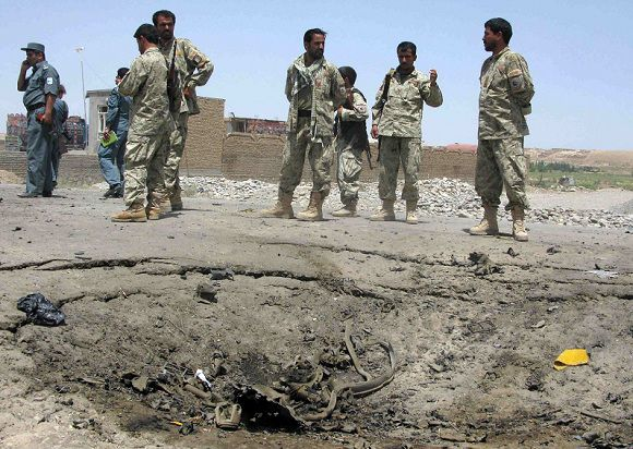 Caption: Afghan policemen stand next to a crater on a road after a suicide car bomb blast in Kunduz June 19, 2011. Three civilians were killed and eleven wounded when a suicide bomber in a car attacked a convoy of foreign troops in northern Kunduz province, the Interior Ministry said. REUTERS/Wahdat (AFGHANISTAN - Tags: CIVIL UNREST CONFLICT CRIME LAW)