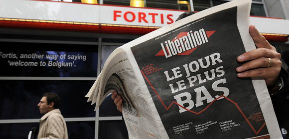 "A pedestrian reads a French daily commenting the financial crisis in front of a Fortis bank on October 07, 2008, in Brussels. Fortis shareholders on October 6, 2008 mulled legal action after French bank BNP Paribas agreed a deal with the Belgian and Luxembourg governments to carve up the troubled finance group. Newspaper's frontpage reads ""The Worst Day"" AFP PHOTO / JOHN THYS"