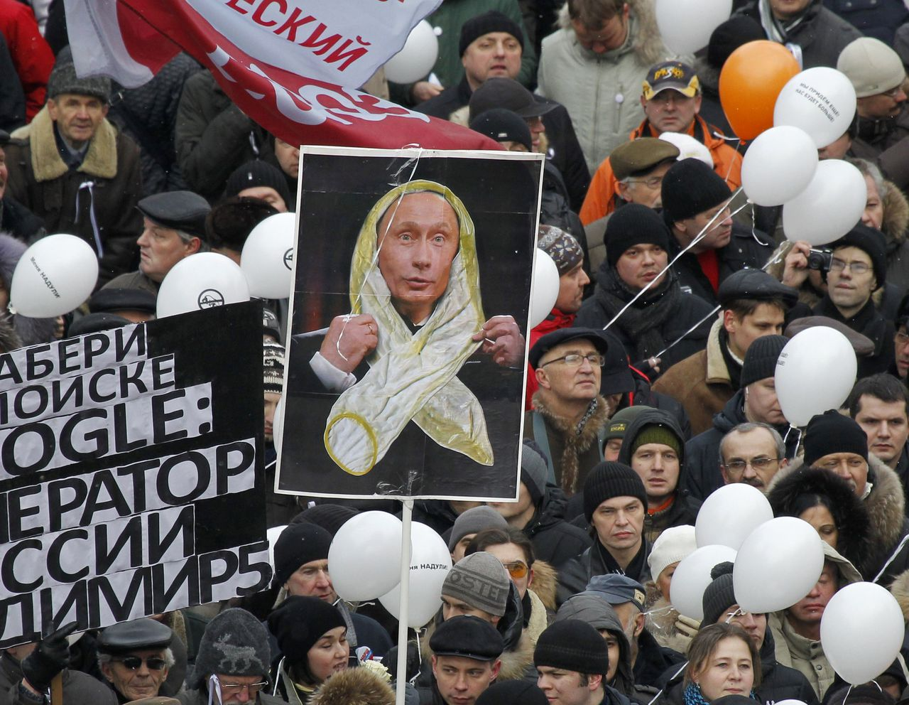 Protesters hold placards, balloons and flags during a demonstration against recent parliamentary election results in Moscow December 24, 2011. Tens of thousands of flag-waving and chanting protesters called on Saturday for a disputed parliamentary election to be rerun, increasing pressure on Vladimir Putin as he seeks a new term as Russian president. The central placard makes a reference to Putin's remarks that he mistook white ribbons worn by protesters for condoms. REUTERS/Denis Sinyakov (RUSSIA - Tags: POLITICS CIVIL UNREST)