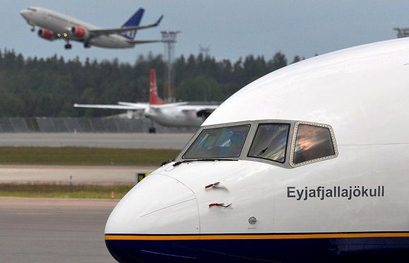 Caption: An SAS Boeing 737 aircraft takes off behind Icelandair's stranded Boeing 757 aircraft named after the Icelandic volcano Eyjafjallajokull is parked at a remote stand at Arlanda airport north of Stockholm, Monday May 23, 2011. The Eyjafjallajokull aircraft is parked at Arlanda, unable to return home, after an ash cloud from the volcano Grimsvotn closed airports in Iceland Sunday. The European Union says ash from an Icelandic volcano could soon affect the airspace over Britain and Ireland. (AP Photo/Scanpix/Johan Nilsson) SWEDEN OUT