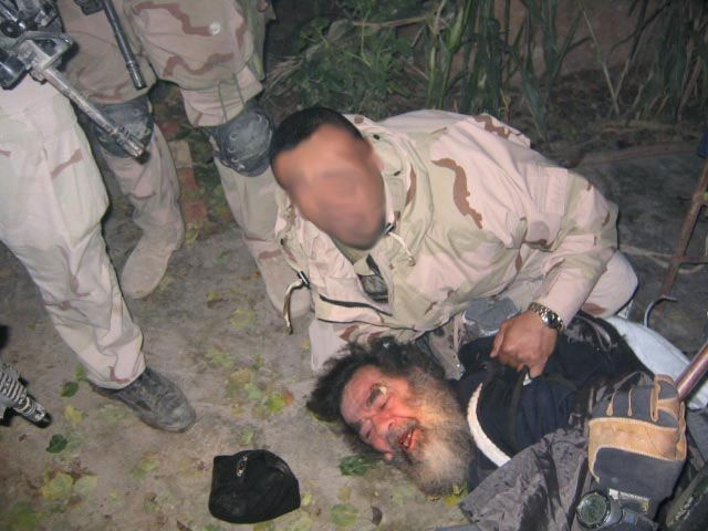 """December 13, 2003, Adwar, Iraq: A bearded and disoriented Iraqi President Saddam Hussein was captured Saturday December 13, at 8:30 p.m. in a specially prepared """"spider hole"""" in a house in Adwar, a town 10 miles from Tikrit, said Lt Col. Ricardo Sanchez, the top U.S. military commander in Iraq. The hole was six to eight feet deep, with enough space to lie down, camouflaged with bricks and dirt and supplied with an air vent to allow long periods inside. Hussein had been in hiding since the US troops entered Baghdad in April 2003.. Credit: Courtesy Military.com / Polaris"""