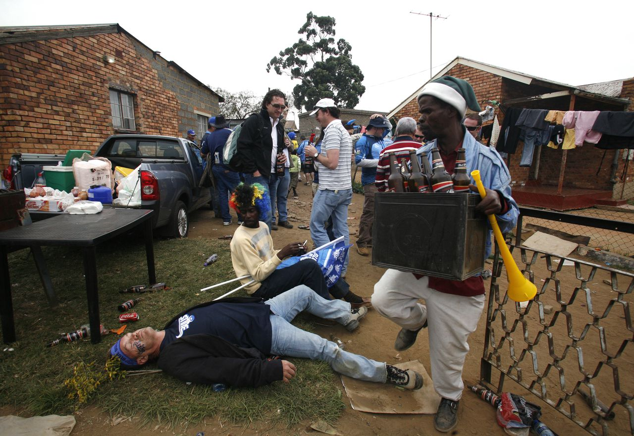 A man carrying empty beer bottles avoids a Bulls supporter who is lying on the grass at a local 'shebeen' or bar before a kick-off for the finals of the Super 14 rugby match against Stormers at the Orlando stadium in Soweto, South Africa, Saturday, May 29, 2010. (AP Photo / Themba Hadebe)
