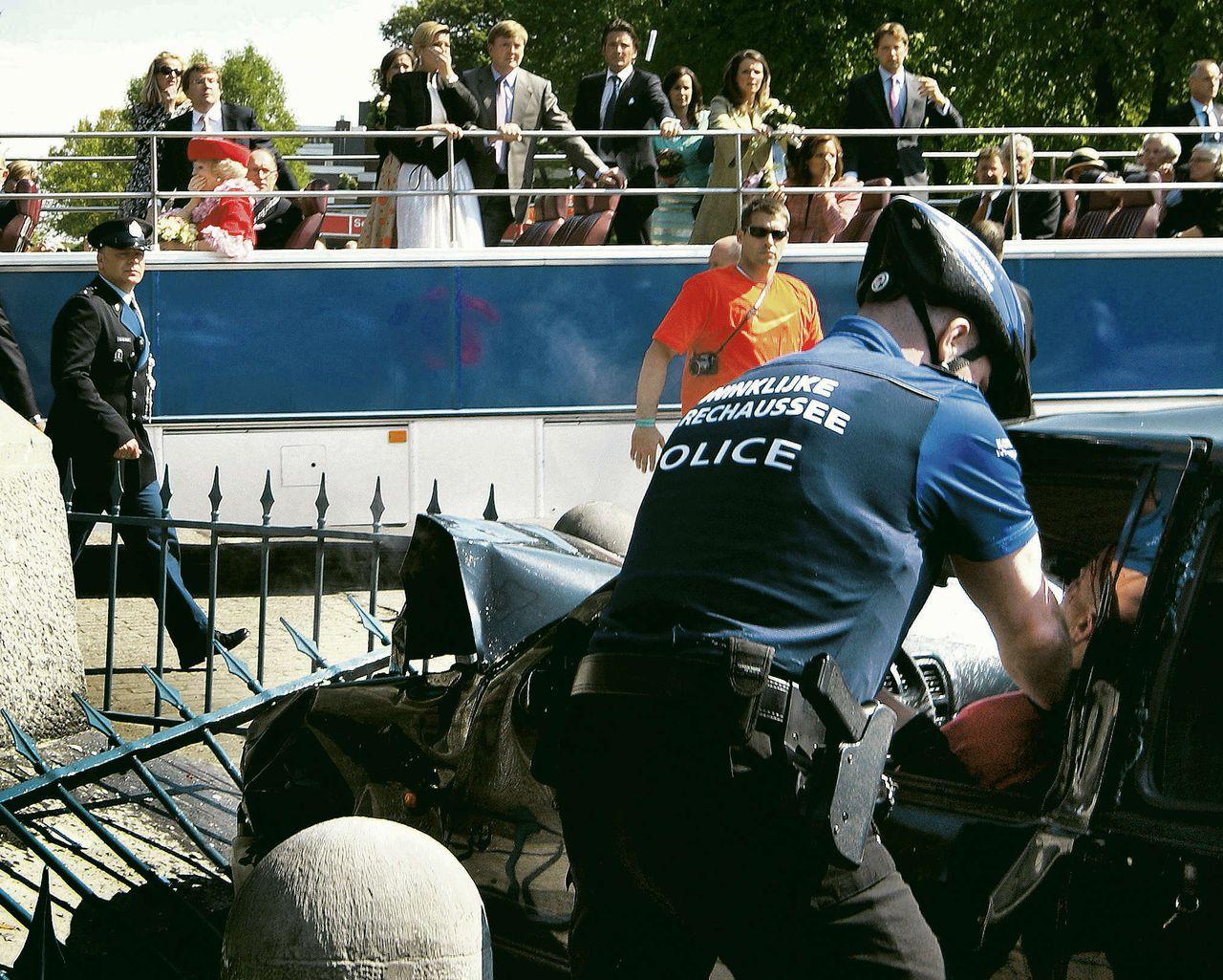 Een politieagent ontfermt zich over Karst T. na diens aanslag in Apeldoorn, Koninginnedag 2009. Op de achtergrond passeert de bus met de koninklijke familie.