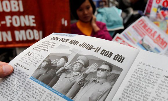 Caption: A resident reads an article on the death of North Korean leader Kim Jong-il in Hanoi December 20, 2011. Kim Jong-il died on a train trip on Saturday, state television reported on Monday, sparking immediate concern over who is in control of the reclusive state and its nuclear programme. REUTERS/Kham (VIETNAM - Tags: POLITICS OBITUARY)