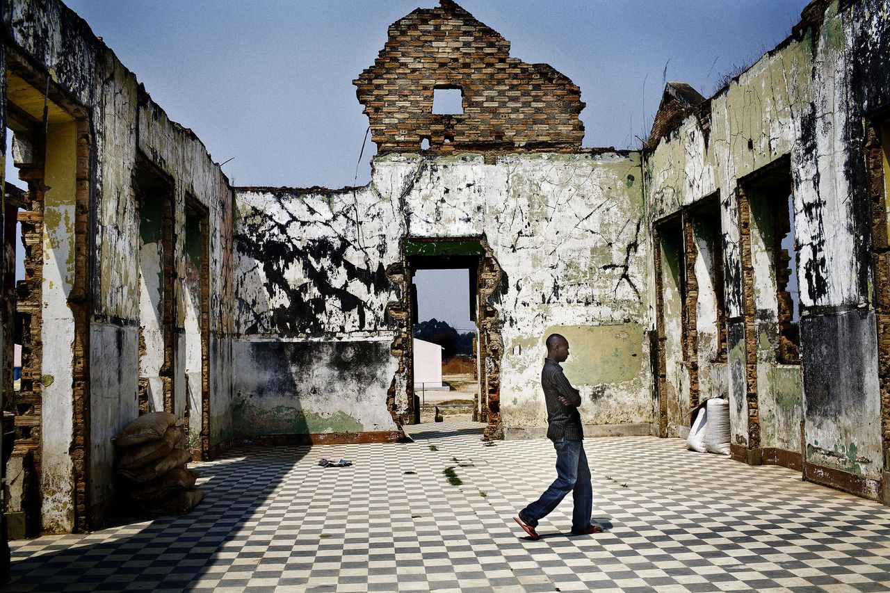 Een van de vele verwoeste gebouwen in de stad Huambo, het Dresden van Angola. Zes jaar na het einde van de burgeroorlog is de wederopbouw nog in volle gang Foto AFP ==== An Angolan man walks trough a destroyed building in Humbo, in south-western Angola, on September 2, 2008. The ruling Popular Movement for the Liberation of Angola (MPLA), which has been in power since independence 33 years ago, will compete in the legislative poll against 13 coalitions and political parties including main opposition Union for the Total Independence of Angola (UNITA). Presidential elections are scheduled for next year. AFP PHOTO/GIANLUIGI GUERCIA