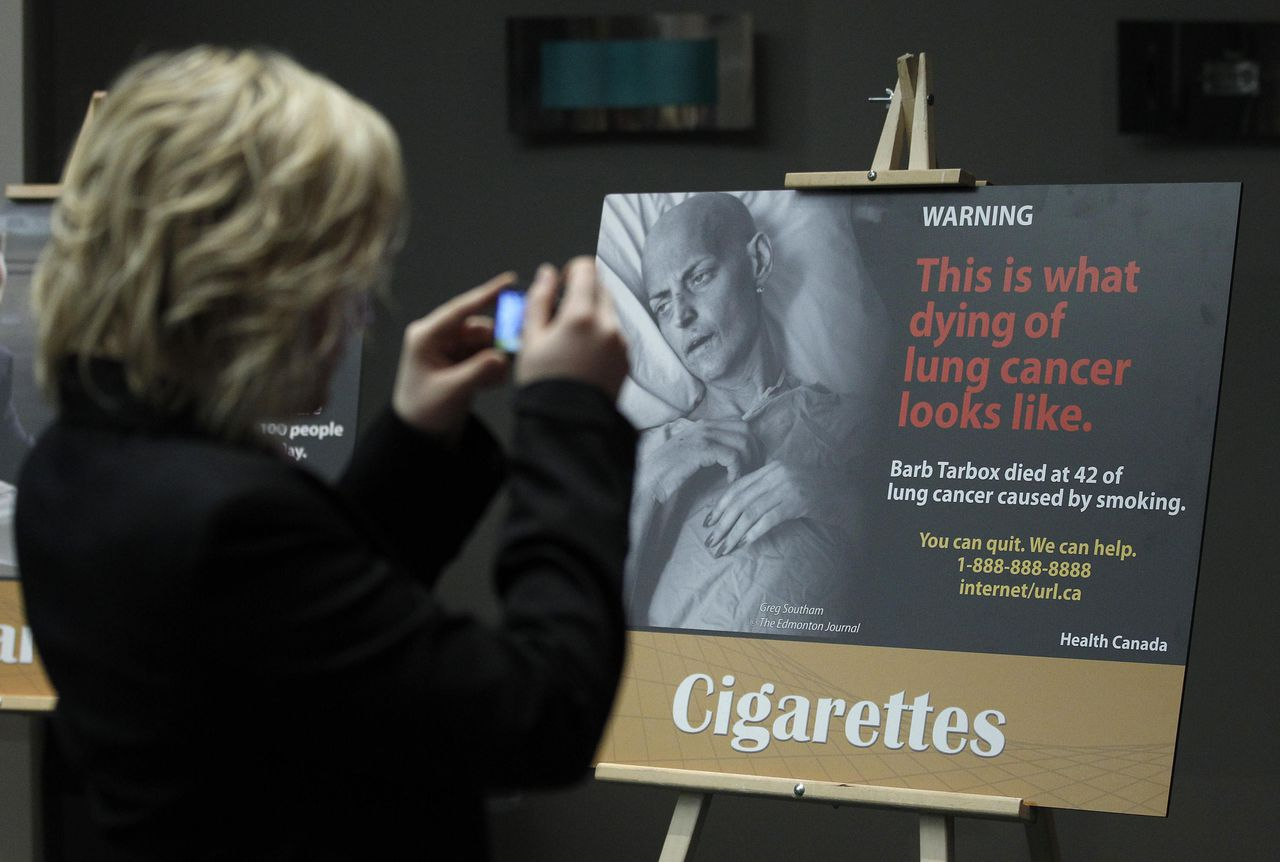 A woman takes a photo of a display showing new warning labels for cigarette packages following a news conference in Ottawa December 30, 2010. REUTERS/Chris Wattie (CANADA - Tags: POLITICS HEALTH)