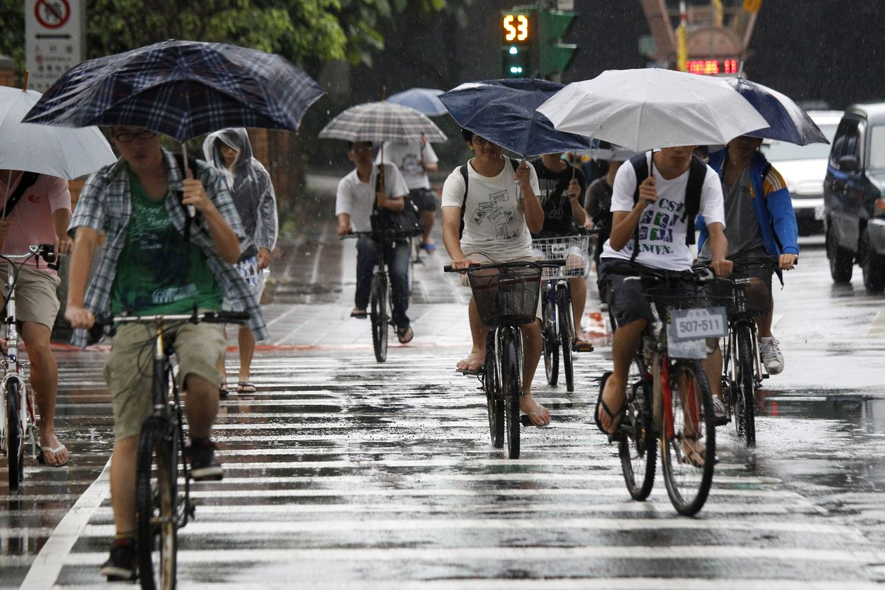 Students cross an intersection in the rain as tropical storm Talim approaches Wednesday, June 20, 2012 in Taipei, Taiwan. More than 2,000 people evacuated from homes as the tropical storm causes flooding in Taiwan. (AP Photo/Wally Santana)