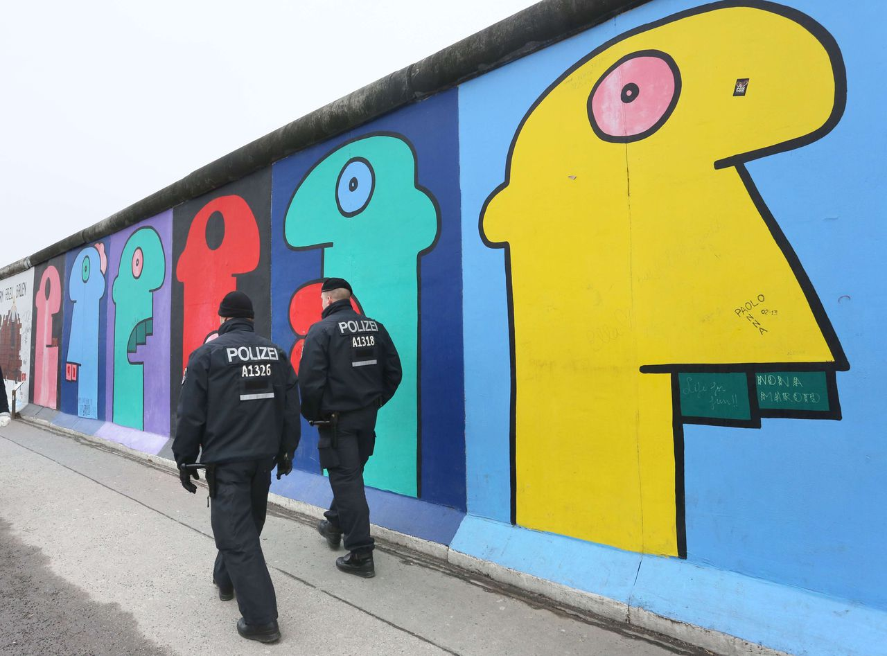 """Policemen walk past a part of the so called East Side Gallery in Berlin on February 26, 2013. The group """"Mediaspree versenken!"""" (Sink Mediaspree!), members of local action groups and a commission of clubs neighbouring the Spree border at the former Berlin Wall's death zone are protesting against the planned demolition of parts of the East Side Gallery in order to construct luxury appartments. The East Side Gallery stretch of the Berlin Wall was taken over by artists who decorated the yet untouchable east side with artwork and political statements, after the wall was taken down in 1989-1990. AFP PHOTO / STEPHANIE PILICK GERMANY OUT"""