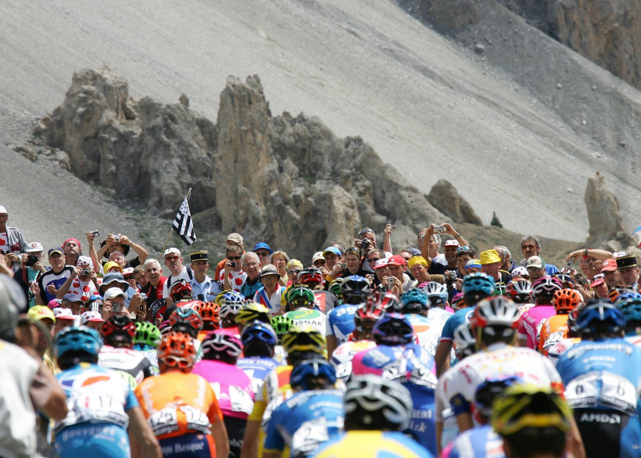 Spectators watch the pack riding in the Col d'Izoard during the 187 km fifteenth stage of the 93rd Tour de France cycling race from Gap to L'Alpe d'Huez, 18 July 2006. AFP PHOTO / FRANCK FIFE