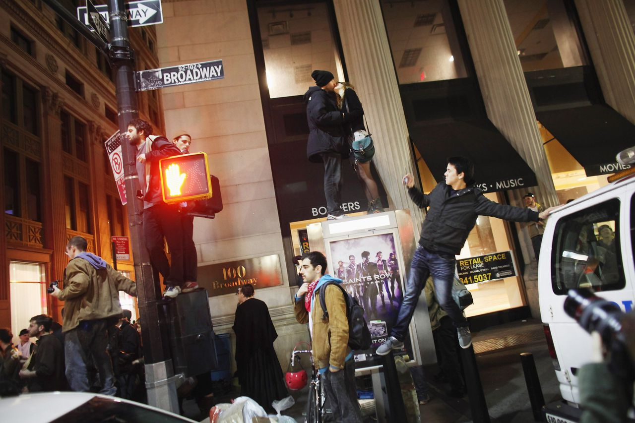 NEW YORK, NY - NOVEMBER 15: Occupy Wall Street protesters stand on a light pole and a pay phone after the police in riot gear removed the protesters the protesters early in the morning from Zuccotti Park on November 15, 2011in New York City. Hundreds of protesters, who rallied against inequality in America, have slept in tents and under tarps since Sept. 17 in Zuccotti Park and has since become the epicenter of the global Occupy movement. The raid in New York City follows recent similar moves in Oakland, California, and Portland, Oregon. Spencer Platt/Getty Images/AFP == FOR NEWSPAPERS, INTERNET, TELCOS & TELEVISION USE ONLY ==
