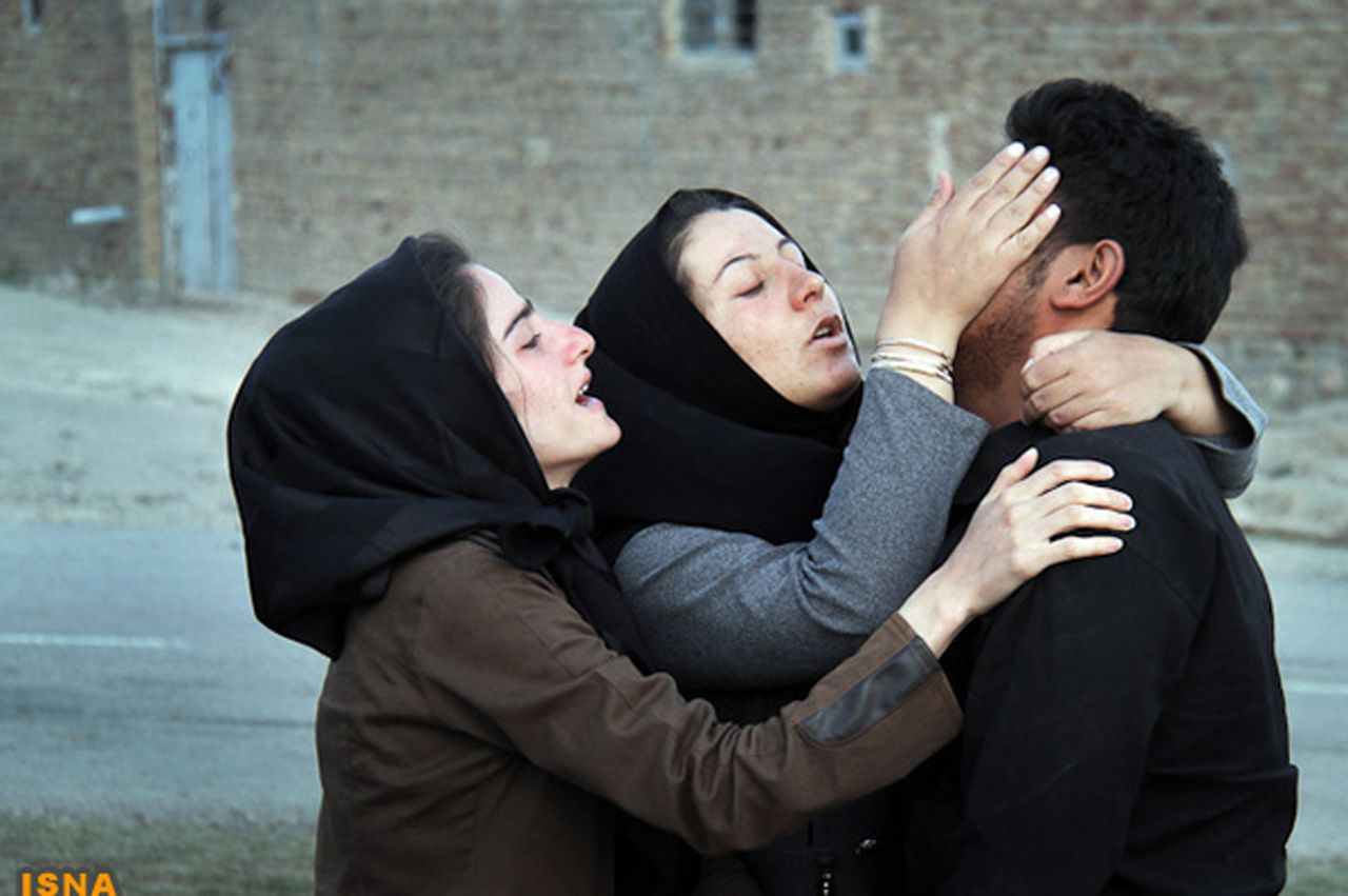 Earthquake victims console each other in the earthquake-stricken town of Azerbaijan in Iran, August 13, 2012. Rescue workers in Iran on Tuesday recovered more bodies three days after two powerful earthquakes struck the northwest of the country, killing more than 300 people, but officials played down reports that casualty numbers may still sharply rise. Picture taken August 13, 2012. REUTERS/Farshid Tighehsaz/ISNA (IRAN - Tags: DISASTER ENVIRONMENT) FOR EDITORIAL USE ONLY. NOT FOR SALE FOR MARKETING OR ADVERTISING CAMPAIGNS. THIS IMAGE HAS BEEN SUPPLIED BY A THIRD PARTY. IT IS DISTRIBUTED, EXACTLY AS RECEIVED BY REUTERS, AS A SERVICE TO CLIENTS