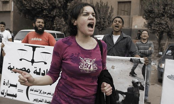 """Caption: An Egyptian activist protests outside a military court on March 11, 2012 during the Trial of the egyptian military doctor Ahmed Adel, who was charged in the case of forced """"virginity tests"""" on female protesters last year in Cairo, Egypt. The Egyptian military court acquitted the doctor accused of conducting the tests in a case that had sparked a national outcry. AFP PHOTO/GIANLUIGI GUERCIA"""