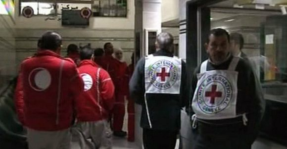 """Caption: An image grab taken off the official Syrian TV on February 25, 2012 shows Red Crescent and Red Cross medics at a hospital in the Syrian city of Homs on February 24, 2012 as they attempt to evacuate Syrians wounded in shelling by regime forces as well as some women and children. The Red Cross made a new attempt on February 25 to bring out people trapped in the city of Homs, two of them wounded Western journalists, after a first successful rescue of civilians. AFP PHOTO/HO/SYRIA TV == RESTRICTED TO EDITORIAL USE - MANDATORY CREDIT """"AFP PHOTO / SYRIAN TV"""" - NO MARKETING NO ADVERTISING CAMPAIGNS - DISTRIBUTED AS A SERVICE TO CLIENTS =="""