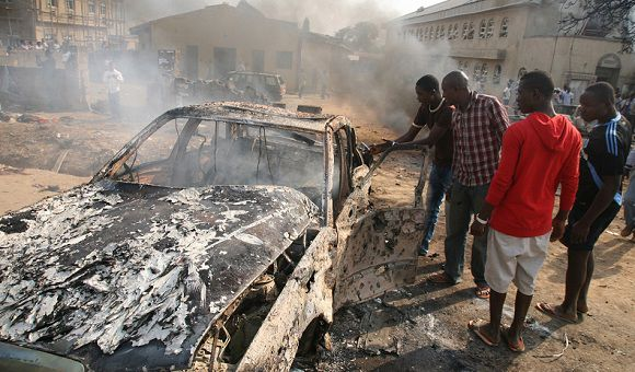 Caption: Men look at the wreckage of a car following a bomb blast at St Theresa Catholic Church outside the Nigerian capital Abuja on December 25, 2011. Two explosions near churches during Christmas Day services in Nigeria, including one outside the country's capital, killed at least 28 people amid spiralling violence blamed on an Islamist group. The suspected attacks stoked fear and anger in Africa's most populous nation, which has been hit by scores of bombings and shootings attributed to Islamist group Boko Haram, with authorities seemingly unable to stop them. AFP PHOTO / Sunday Aghaeze