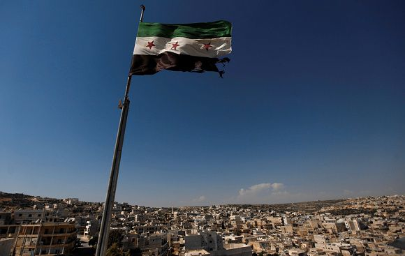 Caption: FILE - In this Tuesday, June 12, 2012 file photo, a Syrian revolutionary flag waves on top of a building on the outskirts of Aleppo, Syria. During two weeks with rebels in northern Syria, three Associated Press journalists found more than 20 rebel groups who often destroy government army posts and convoys but lack the weapons and unity to do more than gradually chip away at the regime of President Bashar Assad _ a recipe for a long, bloody insurgency.(AP Photo/Khalil Hamra, File)