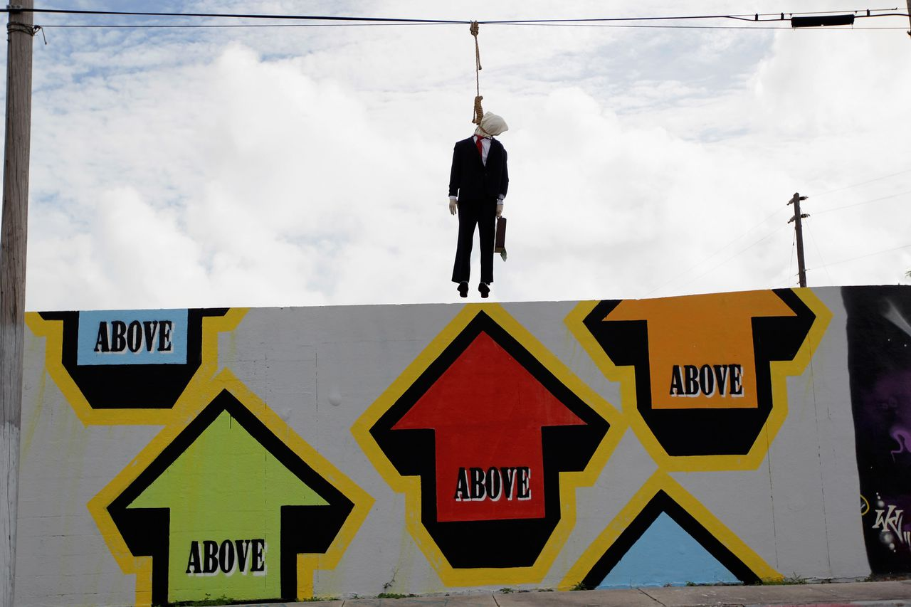 """MIAMI, FL - OCTOBER 28: An effigy dressed as a Wall Street banker hangs from a telephone wire on October 28, 2011 in Miami, Florida. An artist known as Above, created the installation which hangs above a mural that reads """"Give a Wall St. banker enough rope and he will hang himself."""" Joe Raedle/Getty Images/AFP == FOR NEWSPAPERS, INTERNET, TELCOS & TELEVISION USE ONLY =="""