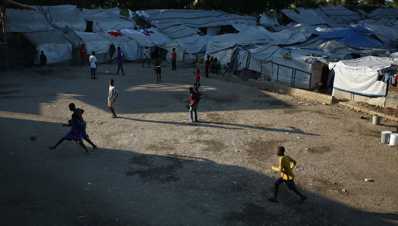 """Children play football in an open area adjacent to their tent city January 5, 2011 in Port-au-Prince. One year after Haiti's earthquake, only five percent of the rubble has been cleared as crippling """"indecision"""" has stalled reconstruction efforts, a new report by humanitarian group Oxfam said. """"This has been a year of indecision and it has put Haiti's recovery on hold,"""" said Roland Van Hauwermeiren, country director for Oxfam in Haiti. AFP PHOTO / Hector RETAMAL"""