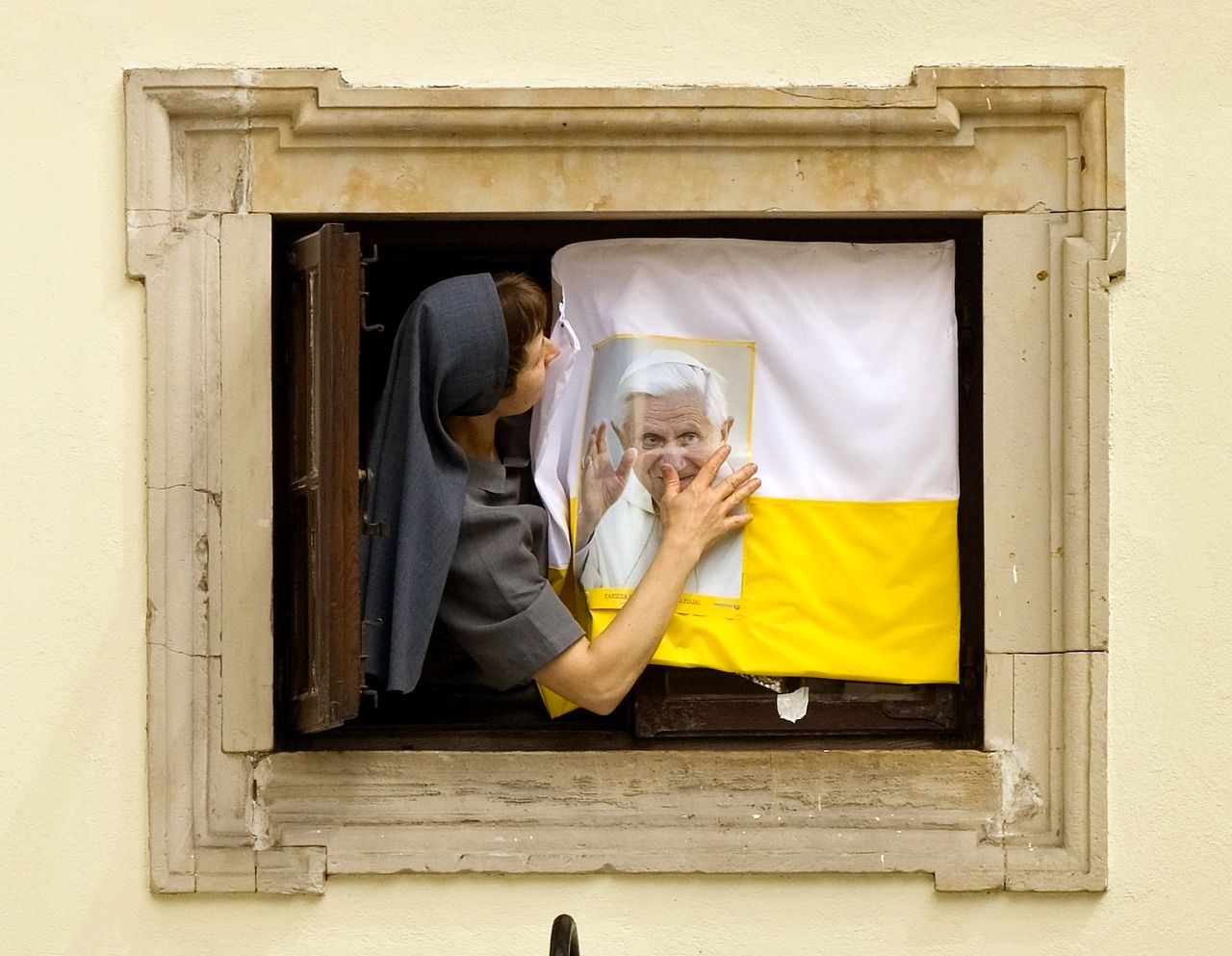 Een Poolse non bevestigt een portret van paus Benedictus XVI en de Vaticaanse vlag op een raam van haar klooster in de oude stad van Warschau. Foto AP A nun fixes a poster of pope Benedict XVI in a window next to the St. John's cathedral in the old town of Warsaw, Poland, Wednesday, May 24, 2006. The pontiff will meet with the clergy in the cathedral on Thursday, May 25, 2006 during his four day visit to Poland. (AP Photo/Vadim Ghirda)