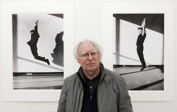 Ger van Elk in 2010 met op de achtergrond twee foto's die van hem zijn gemaakt in 1993 in museum Boijmans van Beuningen in Rotterdam.