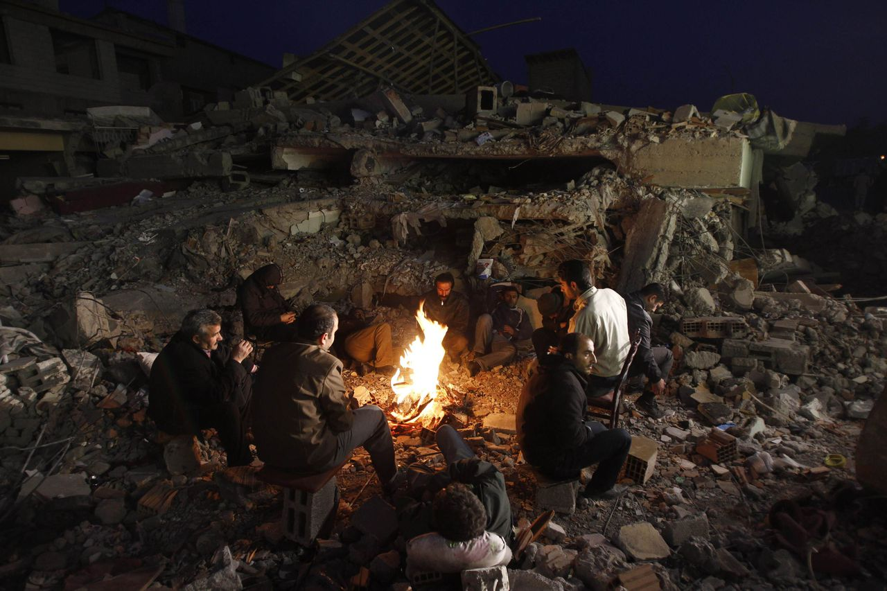 Turkish men sit around a fire amongst collapsed buildings in Ercis, near the eastern Turkish city of Van, October 25, 2011. Tens of thousands of people spent a second night under canvas, in cars or huddled round small fires in towns rattled by aftershocks from the massive earthquake in eastern Turkey that killed hundreds. Early on Tuesday the death toll from Sunday's quake stood at 279 and hundreds more were still missing. Casualties were concentrated so far in Ercis and the provincial capital Van, with officials still checking outlying areas. REUTERS/Baz Ratner (TURKEY - Tags: DISASTER ENVIRONMENT)