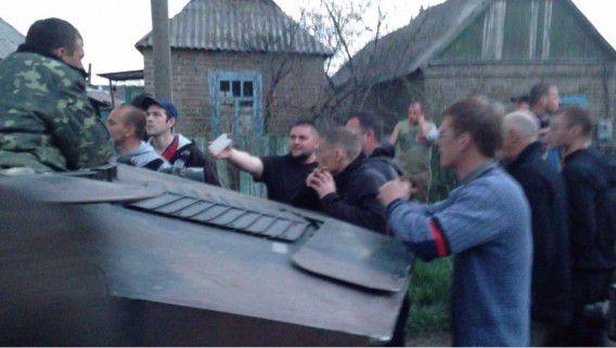 Boze dorpsbewoners slaan op de Oekraïense tank.