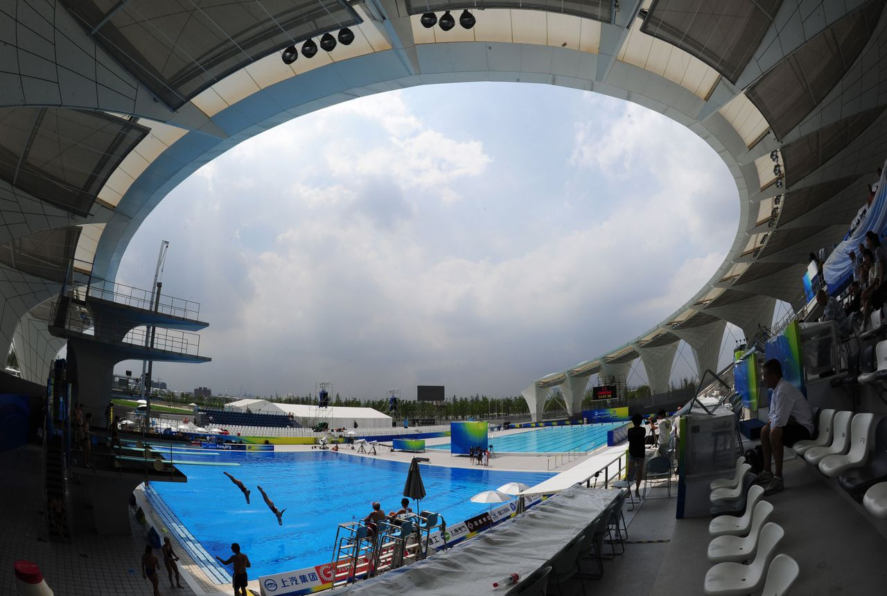 Divers take part in a training session for the FINA World Championships at the outdoor diving swimming pool of the Oriental Sports Center in Shanghai on July 15, 2011. AFP PHOTO / MARK RALSTON