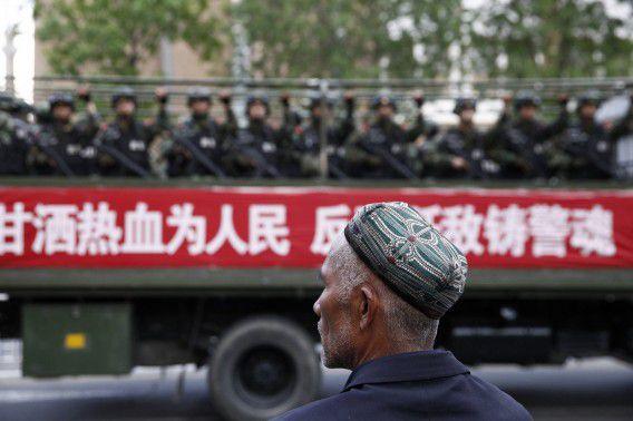 23 mei: Een Oeigoer kijkt toe hoe paramilitairen langsrijden in een truck in Urumqi, de hoofdstad van de onrustige regio Xinjiang.