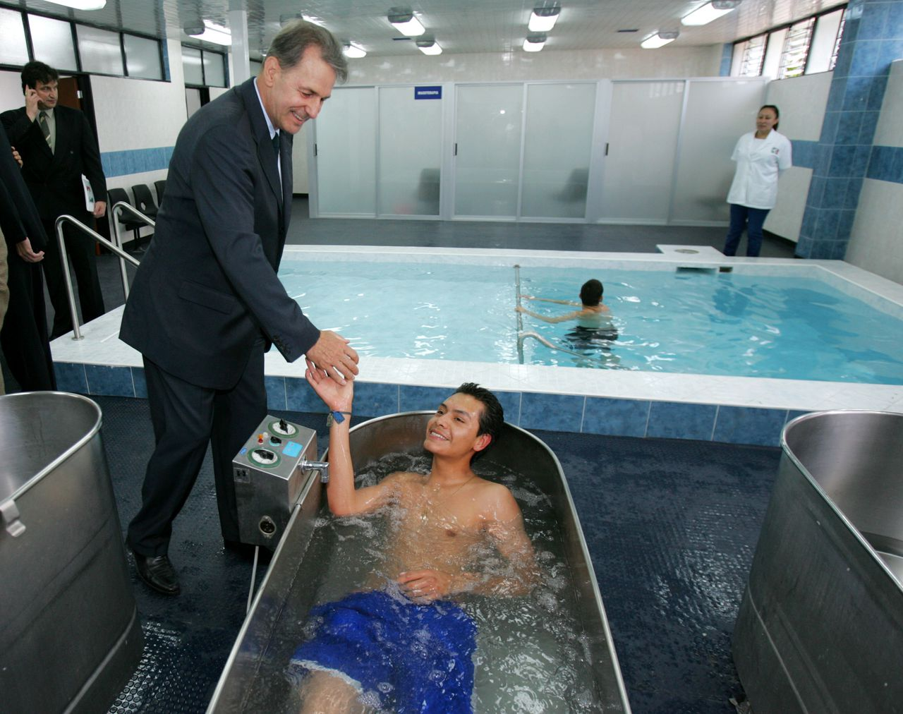 International Olympic Committee President Jacques Rogge, shake hands with Jorge Perez which is recovering in a hydro massage bath at Mexican National Olympic Committee President during a tour and inauguration of newly sports clinic on Friday Sept. 2, 2005, in Mexico City.(AP Photo/Jose Luis Magana)